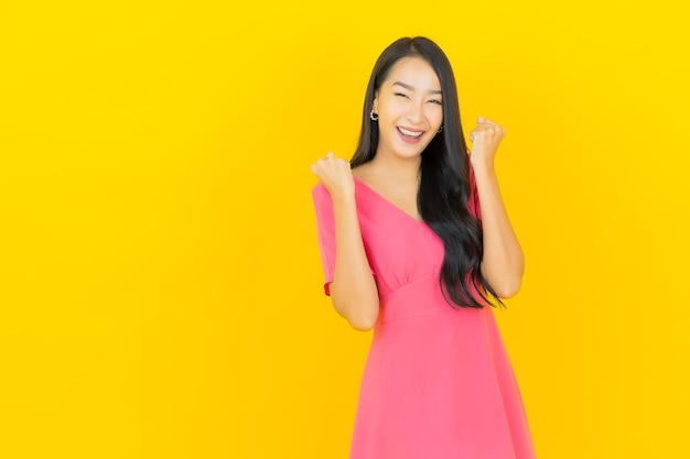 Portret pięknej młodej kobiety azji uśmiecha się w różowej sukience na żółtej ścianie