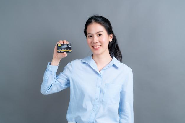 Portret pięknej młodej kobiety azji w niebieskiej koszuli pokazując kartę kredytową z miejsca na kopię na szarej ścianie