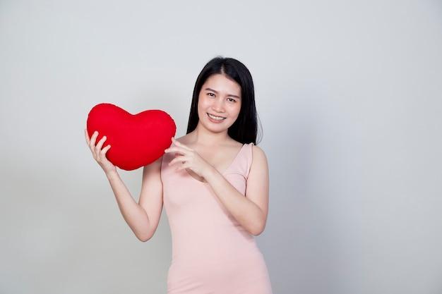 Portret pięknej młodej kobiety azji w sukni pokaż poduszkę w kształcie serca na białym tle na jasnoszarym tle z miejsca na kopię