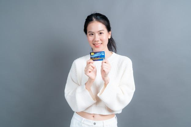 Portret pięknej młodej kobiety azji w sweter pokazując kartę kredytową z miejsca na kopię na szarej ścianie