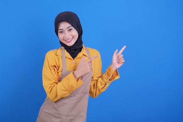 Portret pięknej młodej kobiety azji, wskazując coś niebieskiego