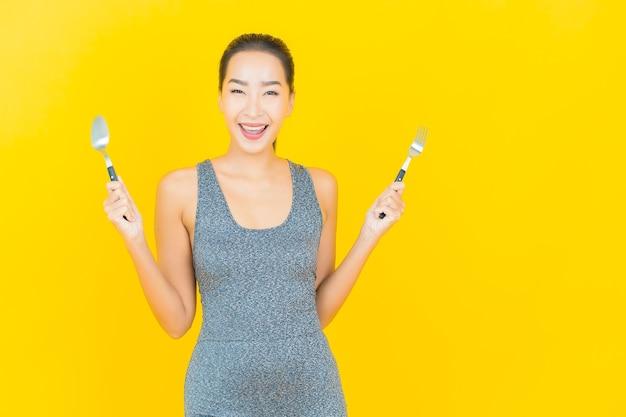 Portret pięknej młodej kobiety azji z odzieży sportowej gotowy do ćwiczeń na żółtej ścianie