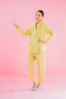 Portret pięknej młodej kobiety biznesu azjatyckich uśmiech w akcji na różowym kolorze