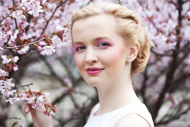Portret pięknej młodej kobiety blond na różowe kwiaty wiśni na wiosnę