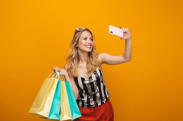 Portret pięknej młodej kobiety blondynka stojącej na białym tle na żółtym tle, biorąc selfie