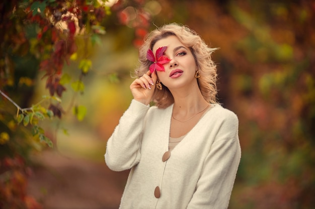 Portret pięknej młodej kobiety blondynka z czerwonym liściem w dłoniach w jesiennym parku.