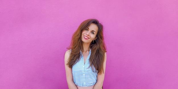 Portret pięknej młodej kobiety brunetka na jasnej różowej ścianie