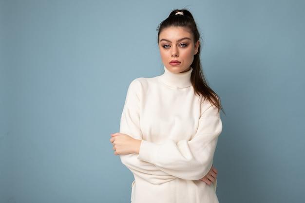 Portret pięknej młodej kobiety brunetka w biały stylowy sweter z założonymi rękami przed nią