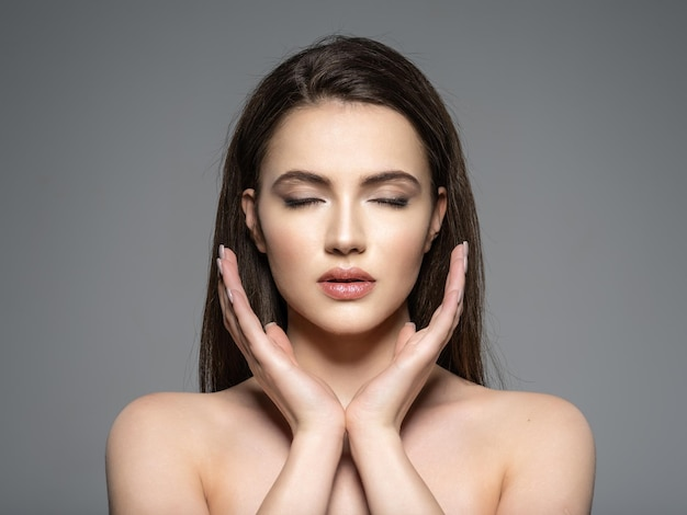Portret pięknej młodej kobiety brunetka z czystą twarz. spokojna twarz. ładny model z zamkniętymi oczami. medytacja