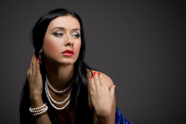 Portret pięknej młodej kobiety brunetka z piękną biżuterią, makijażem i manicure na szarym tle w studio. przestrzeń reklamowa