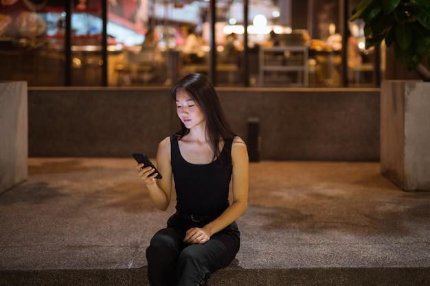 Portret pięknej młodej kobiety chinki na zewnątrz w nocy