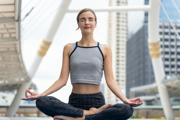 Portret pięknej młodej kobiety ćwiczy joga plenerowy w mieście. piękna kobieta ćwiczyć jogę i medytację, aby zrelaksować się w klasie