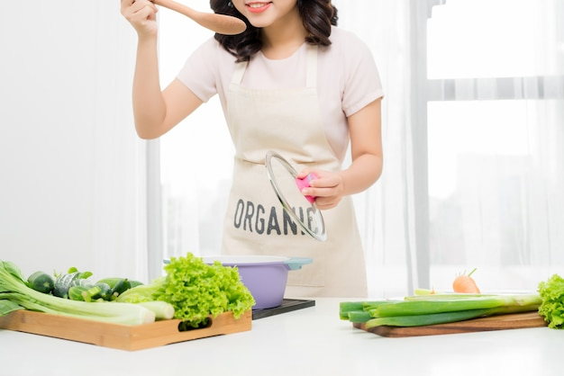 Portret pięknej młodej kobiety gotowania zupy z warzywami w domu.