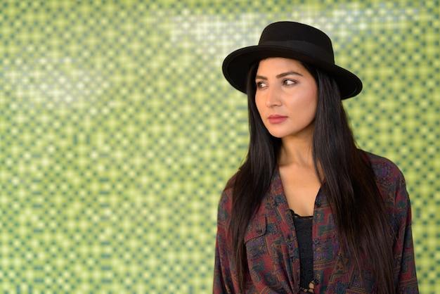 Portret pięknej młodej kobiety myślącej o kolorowej ścianie