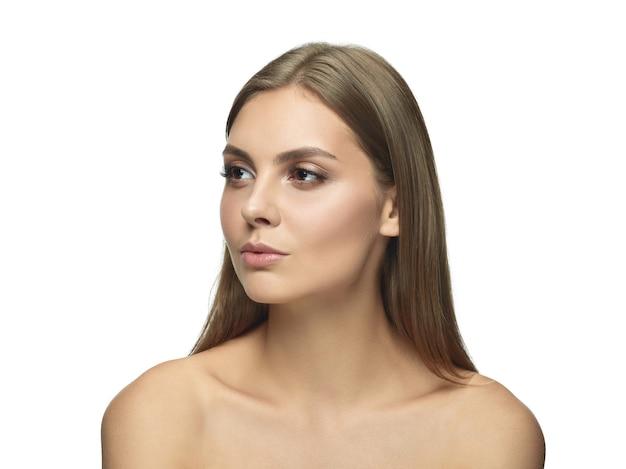 Portret pięknej młodej kobiety na białym tle na białej ścianie. kaukaski modelka patrząc na bok i pozowanie. pojęcie zdrowia i urody kobiet, samoopieki, pielęgnacji ciała i skóry.
