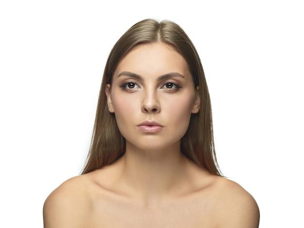 Portret pięknej młodej kobiety na białym tle na białej ścianie. kaukaski zdrowa modelka i pozowanie. pojęcie zdrowia i urody kobiet, samoopieki, pielęgnacji ciała i skóry.