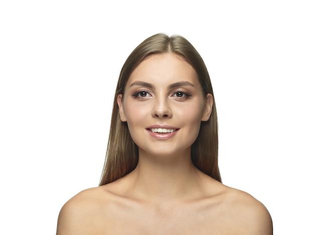 Portret pięknej młodej kobiety na białym tle na białej ścianie. kaukaski zdrowa modelka patrząc na kamery i pozowanie. pojęcie zdrowia i urody kobiet, samoopieki, pielęgnacji ciała i skóry.