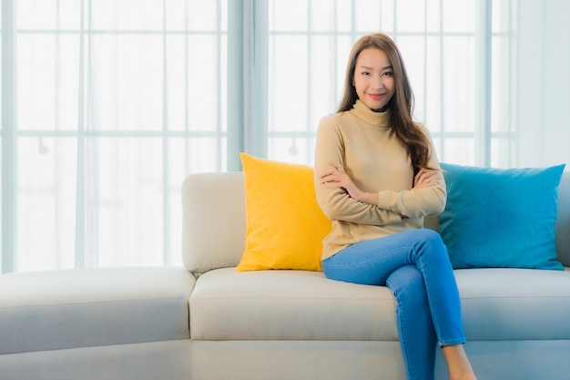 Portret pięknej młodej kobiety na kanapie w salonie