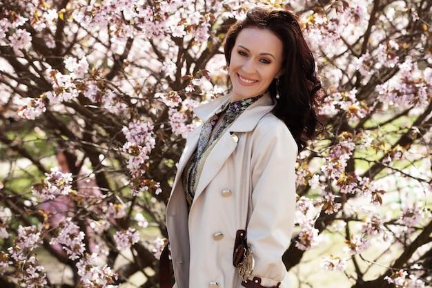 Portret pięknej młodej kobiety na różowe kwiaty wiśni na wiosnę