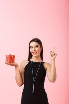 Portret pięknej młodej kobiety na sobie czarną sukienkę stojącej na białym tle na różowym tle, trzymając pudełko, wskazując palcem w górę