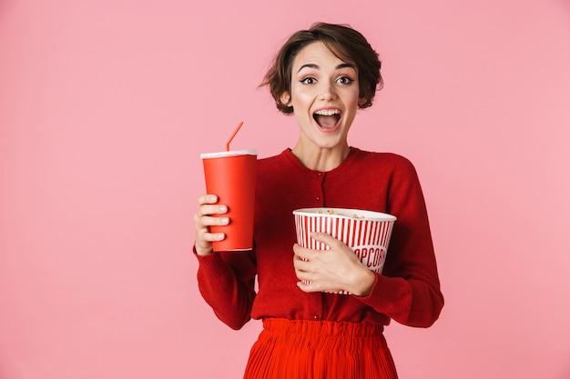 Portret pięknej młodej kobiety na sobie czerwoną sukienkę stojącej na białym tle na różowym tle, trzymając plastikowy kubek z napojem, jedzenie popcornu