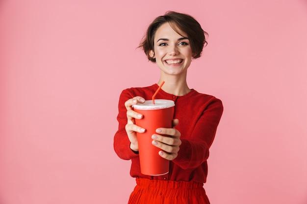 Portret pięknej młodej kobiety na sobie czerwoną sukienkę stojącej na białym tle na różowym tle, trzymając plastikowy kubek z napojem
