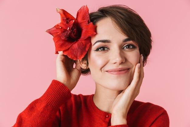Portret pięknej młodej kobiety na sobie czerwoną sukienkę stojącej na białym tle, stwarzających z kwiatem