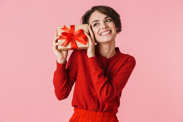 Portret pięknej młodej kobiety na sobie czerwoną sukienkę stojącej na białym tle, trzymając pudełko