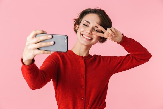 Portret pięknej młodej kobiety na sobie czerwone ubrania stojącej na białym tle, biorąc selfie