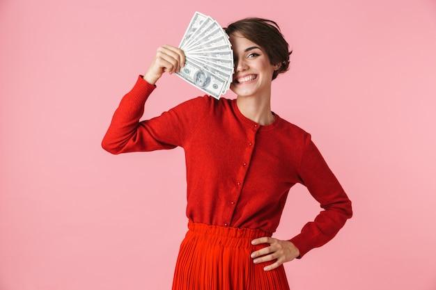 Portret pięknej młodej kobiety na sobie czerwone ubrania stojącej na białym tle nad różowym tle, pokazując banknoty pieniędzy