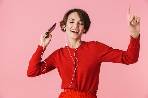 Portret pięknej młodej kobiety na sobie czerwone ubrania stojącej na białym tle, słuchanie muzyki przez słuchawki i telefon komórkowy