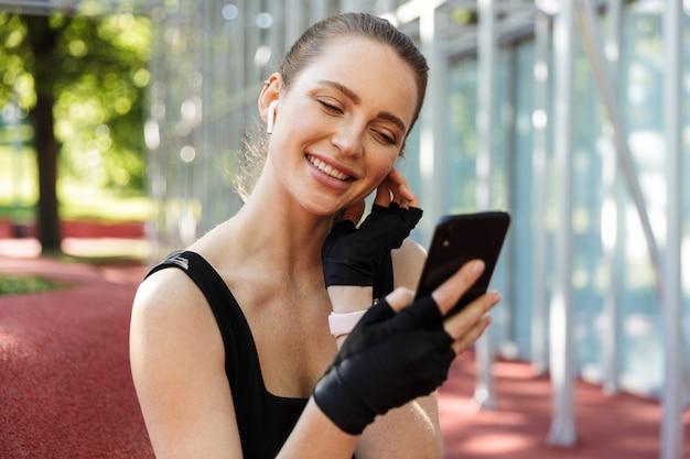 Portret pięknej młodej kobiety noszącej słuchawki douszne, trzymającej smartfon i odpoczywającej po treningu z poziomym metalowym drążkiem na boisku sportowym w zielonym parku