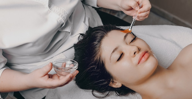 Portret pięknej młodej kobiety o ciemnych włosach leanin z zamkniętymi oczami na łóżku spa robi rutynową pielęgnację skóry w centrum spa.