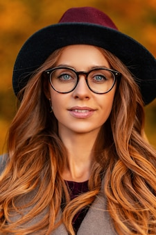 Portret pięknej młodej kobiety o niebieskich oczach i brązowych włosach z naturalnym makijażem w eleganckiej czapce w stylowych okularach w modnym płaszczu. europejski hipster dziewczyna na zewnątrz w parku. jesienny wygląd.