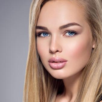 Portret pięknej młodej kobiety o niebieskich oczach i brązowym makijażu. całkiem wspaniała dziewczyna pozuje