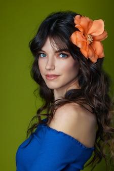 Portret pięknej młodej kobiety o pięknych falowanych włosach z dużym kwiatem we włosach na zielonym tle.