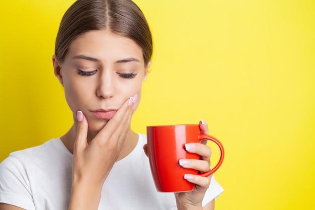 Portret pięknej młodej kobiety odczuwającej bolesny ból zęba.