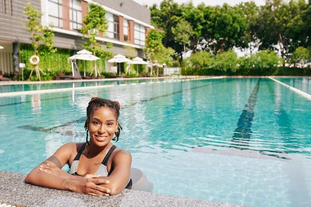 Portret pięknej młodej kobiety orzeźwiającej w basenie uzdrowiska w gorący słoneczny dzień