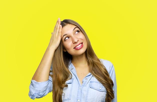 Portret pięknej młodej kobiety patrząc w górę przypomniał sobie coś i trzyma głowę