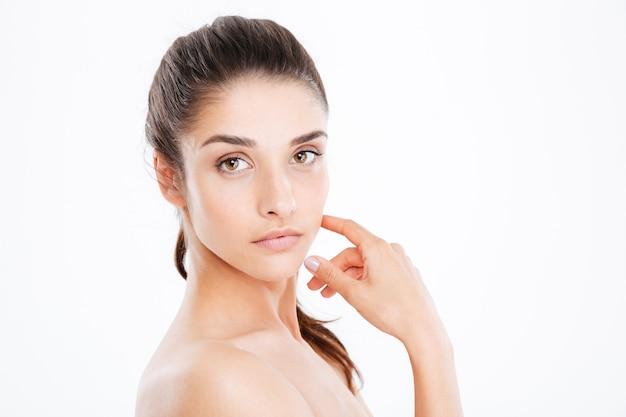 Portret pięknej młodej kobiety patrzącej na przód nad białą ścianą
