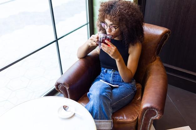 Portret pięknej młodej kobiety picia czerwonej herbaty w kawiarni.
