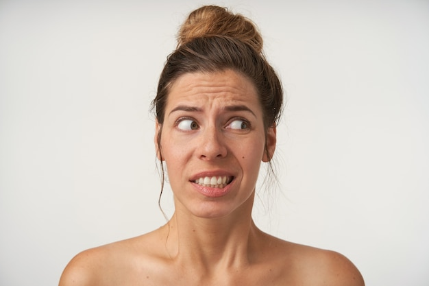 Portret pięknej młodej kobiety pozującej na biało bez makijażu, patrzącej na bok z wątpiącą twarzą, ściągającej brwi i ukazującej zęby