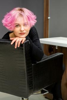 Portret pięknej młodej kobiety rasy kaukaskiej z nową krótką różową fryzurą siedzi na krześle w salonie piękności