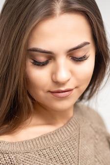 Portret pięknej młodej kobiety rasy kaukaskiej z zamkniętymi oczami po zabiegu przedłużania rzęs i makijażu permanentnym