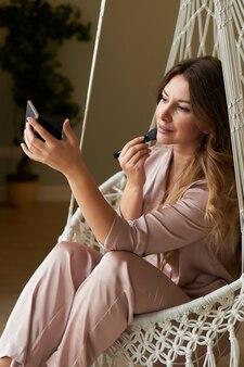Portret pięknej młodej kobiety robi makijaż w domu w pięknym pokoju