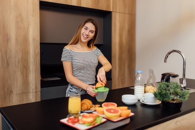 Portret pięknej młodej kobiety robi świeży sok pomarańczowy w nowoczesnej kuchni