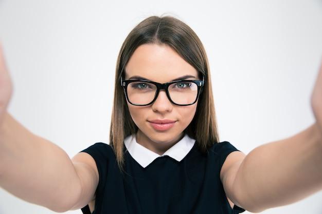 Portret pięknej młodej kobiety robiącej zdjęcie selfie w aparacie na białym tle