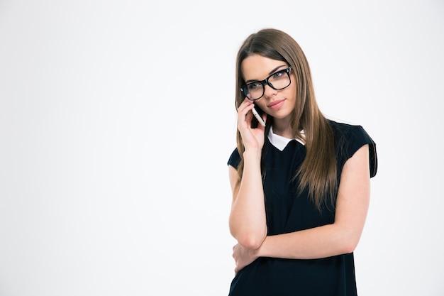 Portret pięknej młodej kobiety rozmawiającej przez telefon na białym tle