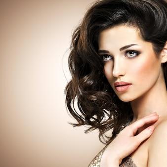 Portret pięknej młodej kobiety sexy kaukaski z włosami broun kręcone. ładna modelka z ciemnobrązowym makijażem oczu