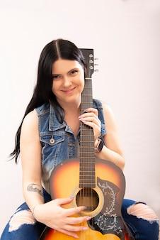 Portret pięknej młodej kobiety sexy z gitarą akustyczną na białym tle